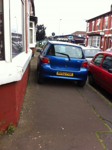 Car driving up the pavement on a residential street